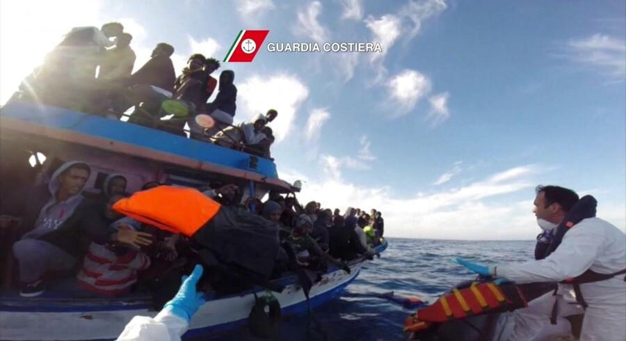 Et screendump viser den italienske kystvagt kaste redningsveste til flytgninge på en overfyldt båd. Foto: AFP