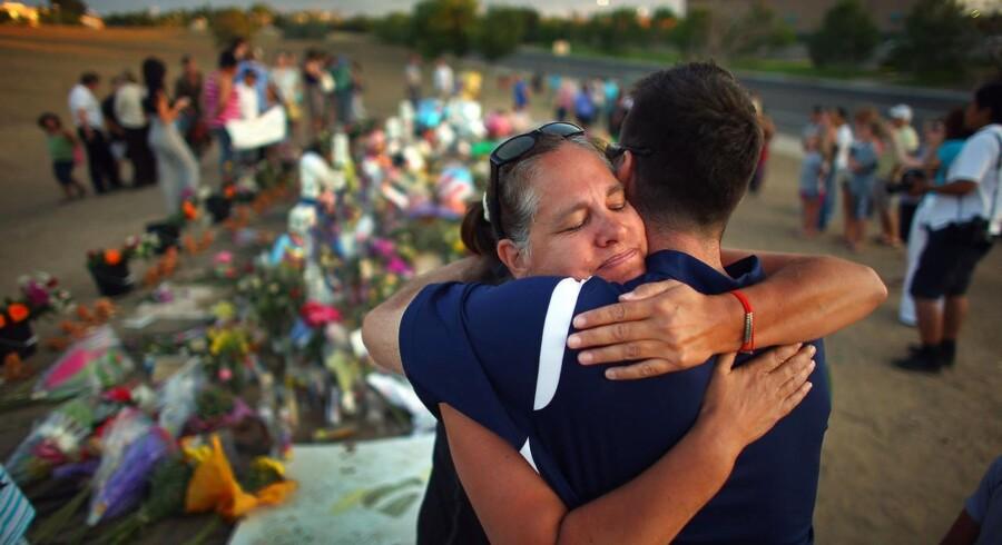 Besøgende krammer hinanden ved blomsterhavet uden for biografen i Denver, hvor 24-årige James Holmes dræbte 12.