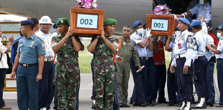 Indonesiske militærfolk bærer to kister med ofre for AirAsia-flystyrtet.