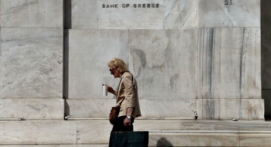 TOPSHOTS A woman walks outside the headquarters of the Bank of Greece in central Athens on June 19, 2015. The European Central Bank's decision-making governing council will hold an emergency session on June 19 to discuss a request from the Bank of Greece for an increase in liquidity to Greek banks. AFP PHOTO / ARIS MESSINIS