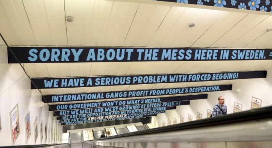 »Vi beklager rodet her i Sverige«, står der på bannere hægtet i loftet i Östermalm Torvs metro i Stockholm.