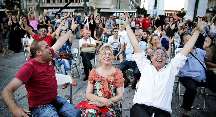 epaselect epa04832732 Supporters of the Syriza party and 'No' vote campaign wave flags and react after the first results of the referendum at Klafthmonos square in central Athens, Greece, 05 July 2015. Greek voters in the referendum were asked whether the country should accept reform proposals made by its creditors. EPA/KAY NIETFELD