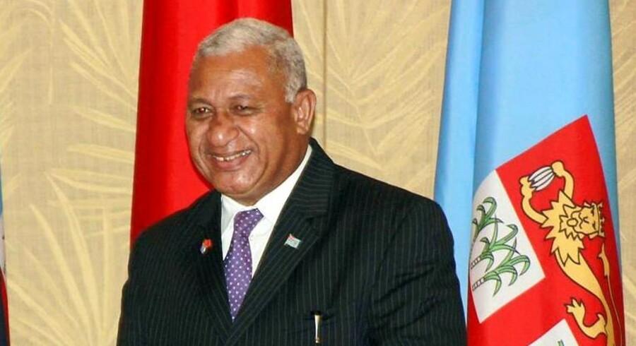 Fijis premierminister, Voreqe Bainimarama. Bag ham anes det lyseblå fijianske flag med et våbenskjold bestående af både den britiske løve og fijianske palmer.