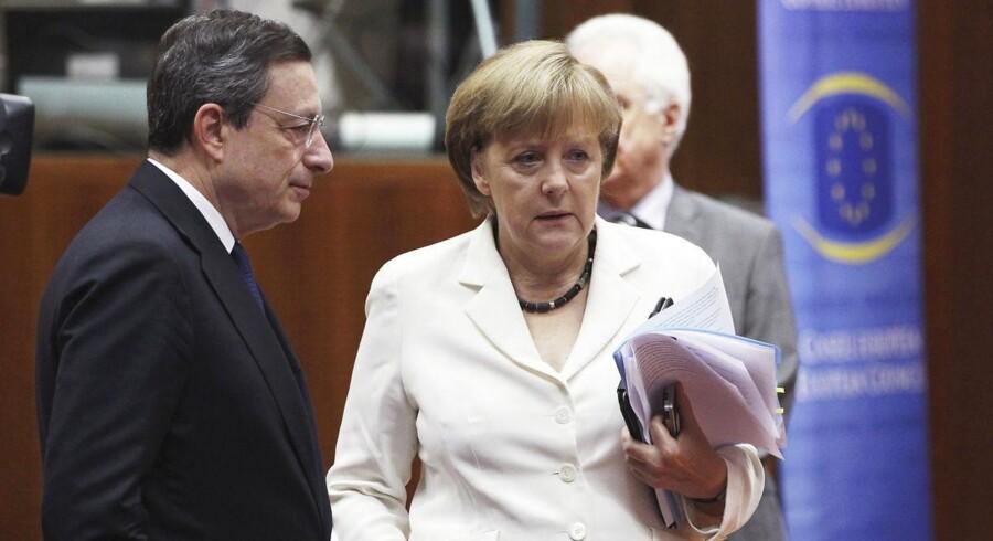 I november var inflationen i eurozonen på blot 0,3 pct. Til venstre ECBs Mario Draghi, til højre Tysklands kansler, Angela Merkel. Arkivfoto.