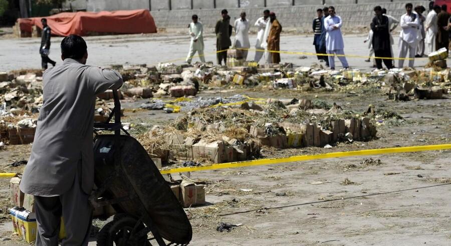 Pakistanske arbejdere samles efter en voldsom eksplosion ved et frugt - og grøntsagsmarked i udkanten af Islamabad 10. april i år. 23 mennesker blev dræbt og omkring 100 sårede.
