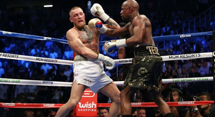 Floyd Mayweather Jr. throws a punch at Conor McGregor during their super welterweight boxing match on August 26, 2017 at T-Mobile Arena in Las Vegas, Nevada. Christian Petersen/Getty Images/AFP