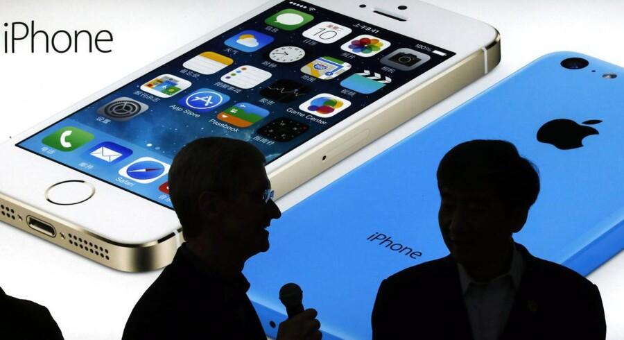 Skyggeprofilerne af Apples topchef, Tim Cook (til venstre), og bestyrelsesformand for verdens største mobilselskab, China Mobile, Xi Guohua (til højre), ses her foran et billede af Apples nyeste iPhone-modeller, da de to i januar efter års forhandlinger skrev kontrakt om salg af iPhone hos China Mobile. Men aftalen er ikke med i Tim Cooks regnskab for julen, som skal vise fremgang, kræver investorerne. Foto: Kim Kyung-Hoon, Reuters/Scanpix