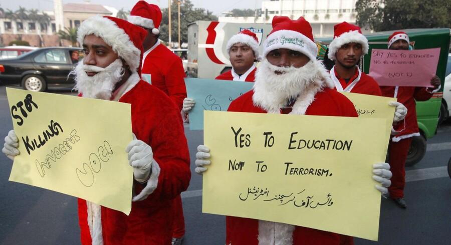 Mænd klædt i julemandskostumer demonstrerer mod Taleban, som har taget ansvaret for massakren på militærskolen i Peshawar.