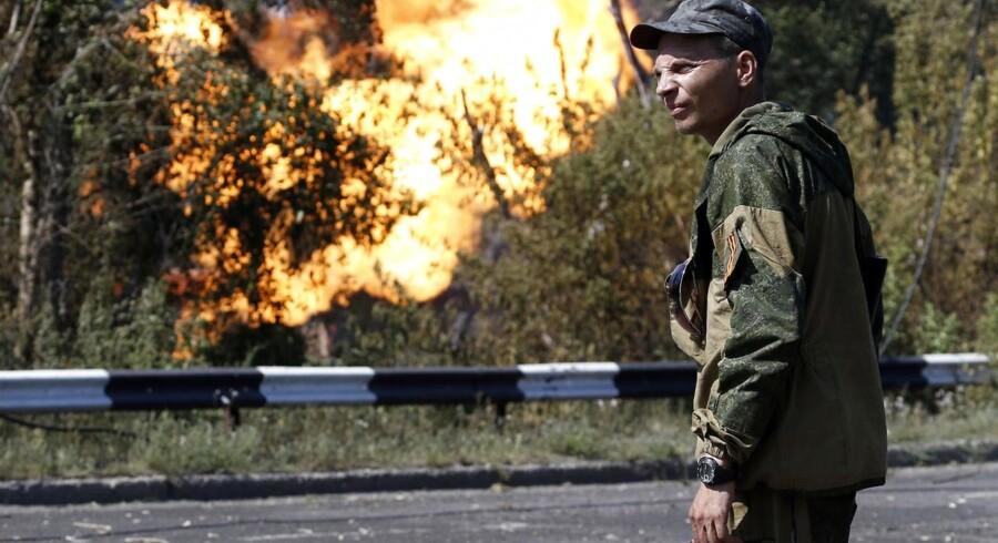 En pro-russisk soldat ser til, mens ilden breder sig fra en gasrørledning, der er blevet bombet nær Donetsk i det østlige Ukraine.