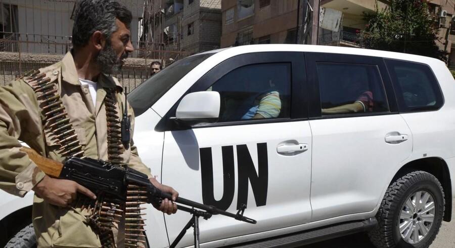 En syrisk oprørssoldat med sit våben, mens han sammen med sine kolleger eskorterer en konvoy af FN-biler med våbeneksperter gennem en af Damaskus' forstæder.