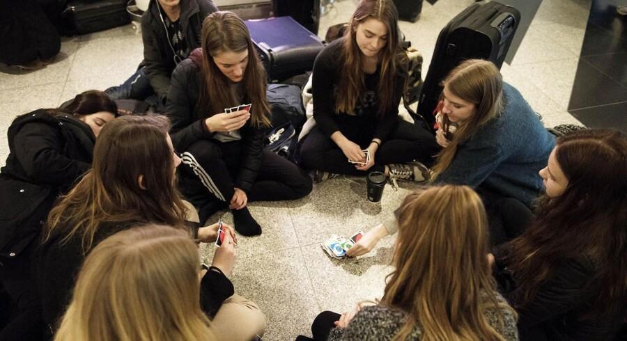 En strejke blandt flyselskabet Norwegians piloter betyder, at selskabet onsdag aflyser en lang række afgange. Strandede passagerer spiller kort på gulvet i Københavns Lufthavn.