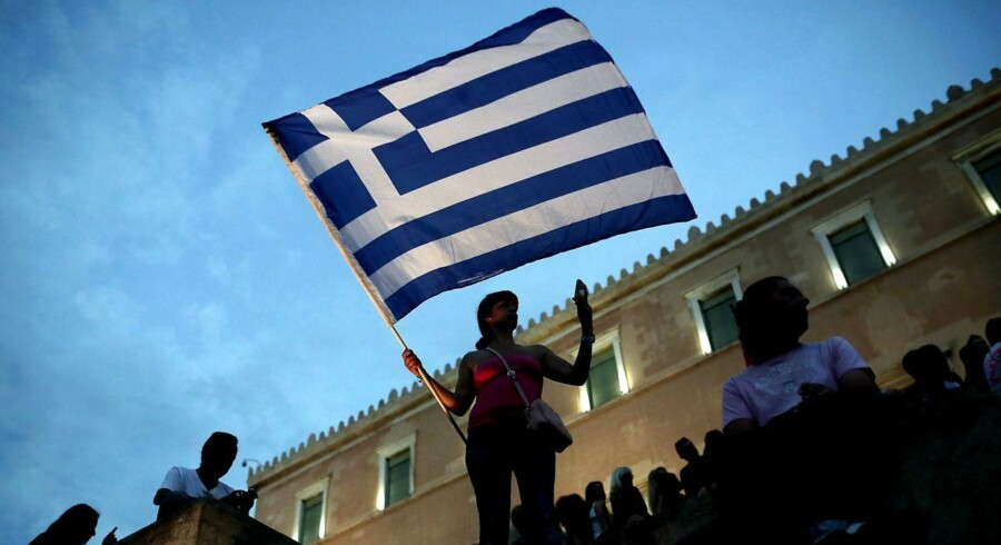 An anti-austerity protester holds a Greek flag in front of the parliament during a protest against austerity policies in Athens on June 21, 2015. With Greece in danger of tumbling into the economic abyss it faces the haunting memory of Argentina in 2001, when the South American country defaulted on nearly $100 billion and was plunged into a crisis it is still battling back from. AFP PHOTO / ANGELOS TZORTZINIS