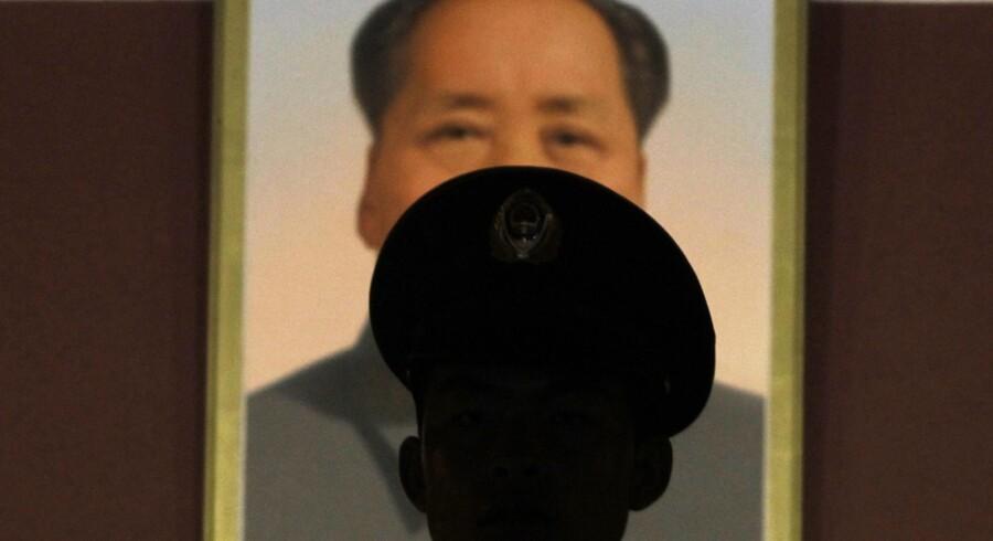 En militærpolitimand står vagt foran Maos portræt ved Den Himmelske Freds Port i Beijing i sidste måned. Heltedyrkelsen af formand Mao fortsætter den dag i dag.