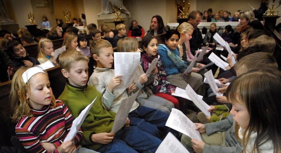 Både børn og vokse synger salmer, og de gør det gerne i fællesskab. Her er det fællessang for skoleelever i Vor Frue Kirke.