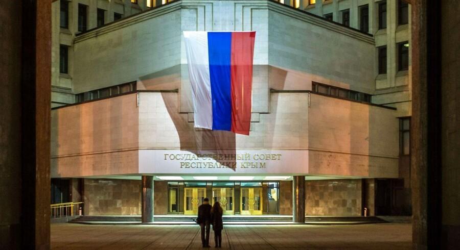 Et russisk flag hænger fra Krims tidligere parlamentsbygning i Simferopol. Ruslands handlinger har betydet vestlige sanktioner, og det får Fitch til at blinke med advarselslampen.