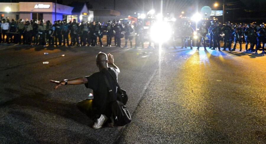 En demonstrant knæler foran det kampklædte politi.