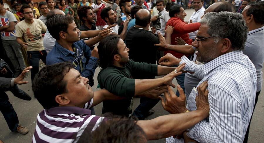 Her slås en gruppe indere for at komme foran i en kø til at komme på et fly tilbage til Indien.