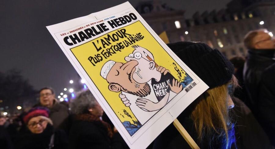 En forsidetegning fra Charlie Hebdo, der forestiller en muslim, der tungekysser med en tegner. Øverst står på fransk: »Kærligheden – stærkere end hadet«.