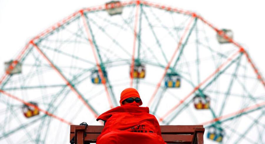 En ældre beboer på cirkus-øen Coney Island skærmer sig for solen under en meget lavthængende paraply.