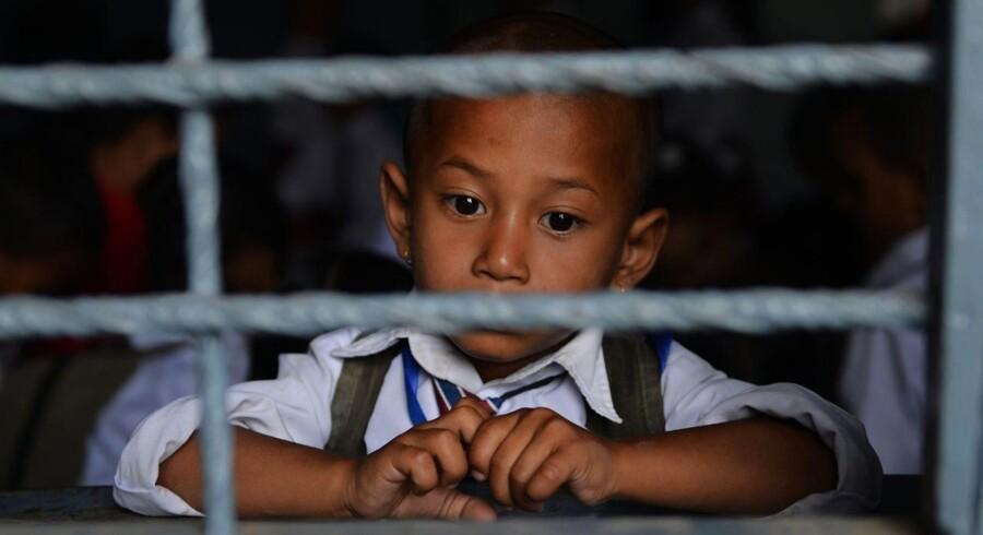 En nepaliesisk skoledreng på fire år kigger ud af vinduet fra dit klasseværelse i Bhaktapur 31. maj.