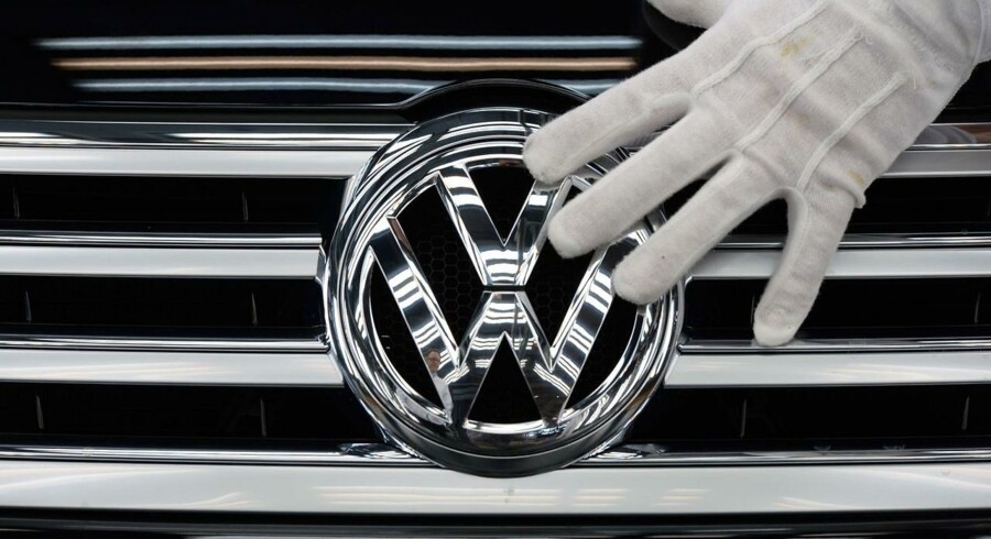Picture taken on October 23, 2015 shows an employee of German car maker Volkswagen (VW) touching the VW logo on a Phaeton car at the company's Glaeserne Manufaktur (Transparent Factory) in Dresden, eastern Germany. German auto giant Volkswagen said on October 28, 2015 that the global pollution-cheating scam it is currently embroiled in pushed it deeply into the red in the third quarter and would hurt earnings for the whole of 2015. AFP PHOTO / DPA / RALF HIRSCHBERGER +++ GERMANY OUT