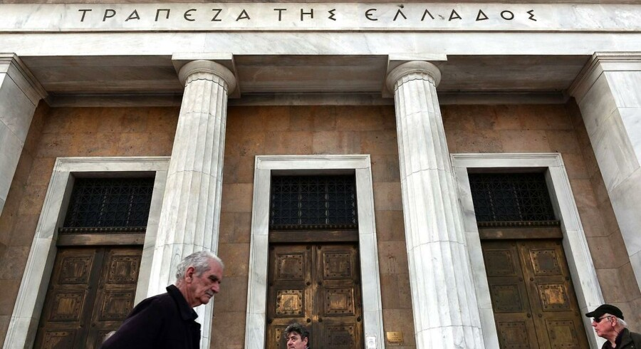 People walk past Bank of Greece headquarters in Athens on February 5, 2015.
