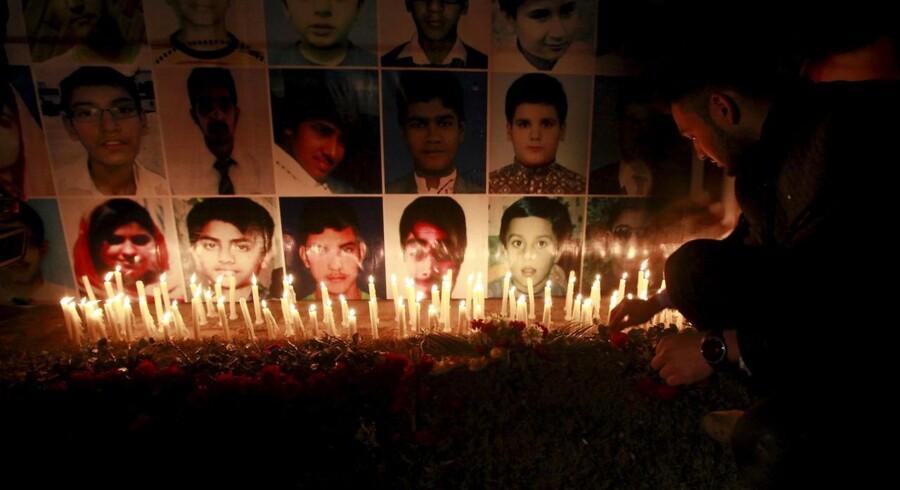 ARKIVFOTO: En mand placerer en rose efter at have tændt et lys ved billederne af ofrene fra massakren mod Army Public School i Pashawaar for godt et år siden. Onsdag blev fire mænd fra taleban-bevægelsen henrettet for at have stået bag udåden..