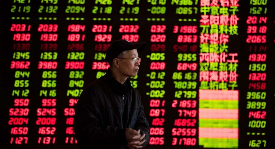 An investor looks at stock informations at a trading hall of a securities firm in Shanghai on January 28, 2014. Chinese shares ended lower on worries over market liquidity, dealers said. AFP PHOTO / JOHANNES EISELE