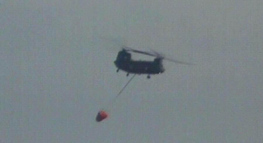Japansk militær forsøger nu atbekæmpe nedsmeltningen på Fukushima-værket fra luften. Her ses helikopteren på vej med vand, som skal kastes ud over reaktorerne.