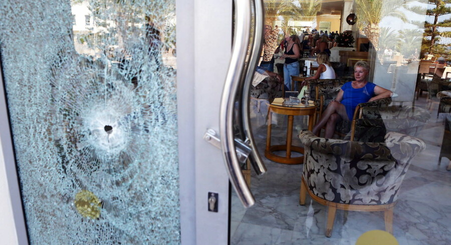 epa04820185 A woman looks toward a glass door shattered by a bullet at Imperial Marhaba Hotel in the resort town of al-Sousse, a popular tourist destination 140 km south of Tunis, Tunisia, June 26 June 2015. According to local reports unknown assailants detonated at least one bomb then opened fire on tourists at two hotels, killing at least 28, including Germans, Brits and Belgians and wounding several others, some while they were sunbathing, at least one of the attackers was killed by Tunisian security services, while a second has been arrested. EPA/MOHAMED MESSARA