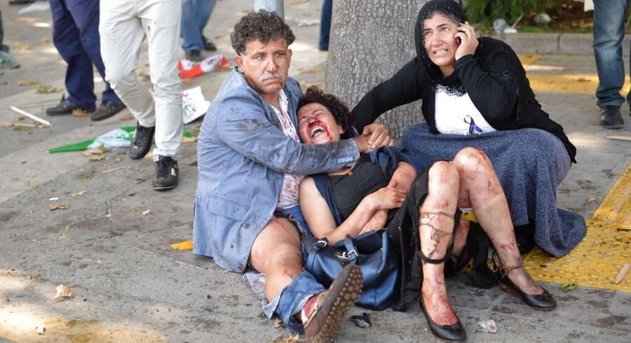 En såret kvinde trøstes efter bombeangrebet i Ankara.