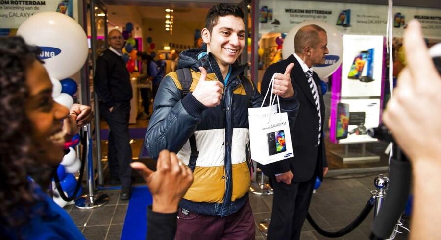En glad køber forlader forretningen i Rotterdam i Holland med den nye Samsung Galaxy S5 i posen ved lanceringen 11. april. Arkivfoto: Remko de Waal, EPA/Scanpix