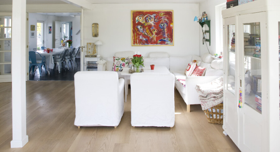 Fra opholdsstuen med den hvide sofagruppe er der et kig ind i spisestuen, hvor der er udgang til haven.