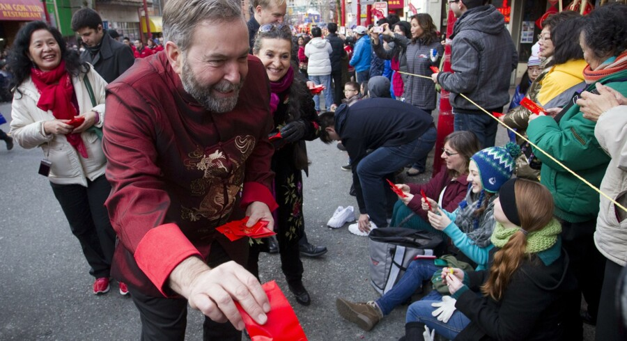 Leader of the New Democratic Party (NDP) Thomas Mulcair hands out gifts during the Chinese New Year parade in Vancouver, British Columbia February 2, 2014. According to the Chinese zodiac the Lunar New Year began on January 31 and marks the start of the Year of the Horse. REUTERS/Ben Nelms (CANADA - Tags: SOCIETY)