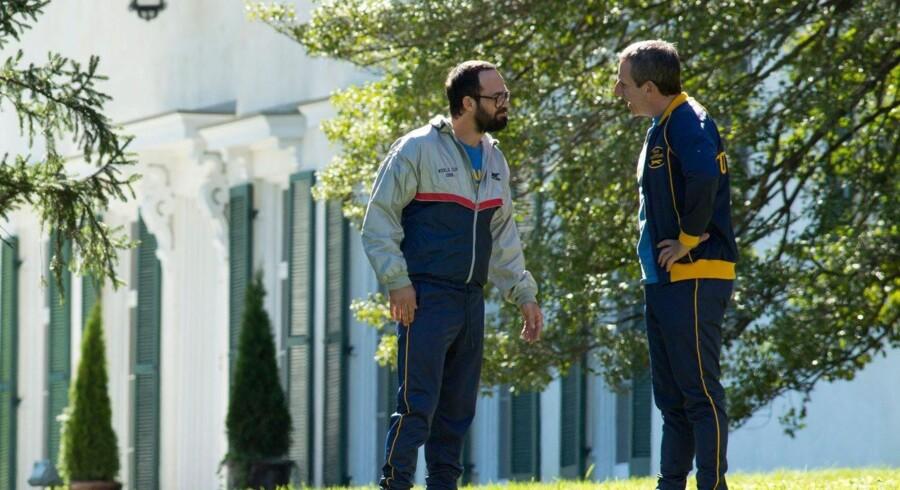 Steve Carell (til højre) er den sportsgale millardær John du Pont, der rekrutterer guldmedaljevinderen Dave Schultz (Mark Ruffalo, til venstre) til sit eget megalomane projekt. Foto: Sony Pictures