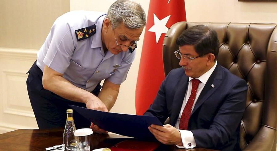Tyrkiets premierminister Ahmet Davutoglu (th) briefes af chefen for det tyrkiske luftvåben general Akin Ozturk på et pressebillede, der er udleveret af premierministerens kontor.