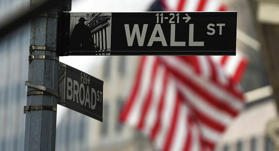 (FILES) This October 16, 2014 file photo shows a Wall Street sign near the New York Stock Exchange (NYSE) building in New York. Wall Street stocks opened higher Tuesday after the Commerce Department unexpectedly raised its estimate for third-quarter US economic growth. The economy grew at a 3.9 percent annual pace in the July-September quarter, stronger than the initial estimate of 3.5 percent as business investment and consumer spending picked up. Analysts had expected the initial estimate to be revised downward. AFP PHOTO/Jewel Samad / FILES
