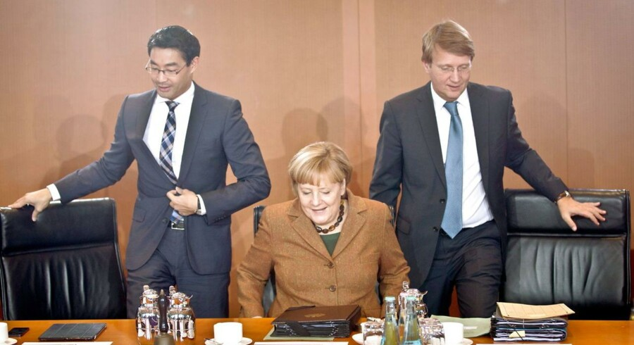 Forbundskansler Angela Merkel mellem sin økonomiministerPhilipp Roesler (tv) og sin stabschef Ronald Pofalla (th) før et kabinetsmøde onsdag efter De Grønne forlod regeringsforhandlingerne.