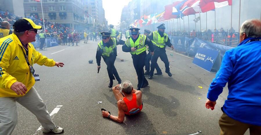 Forskrækkede betjente trækker våbnene, da den første eksplosion lyder nær målstregen til Boston Marathon.