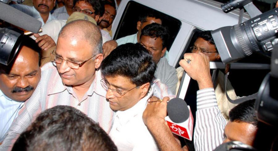 Politiet eskorterer lørdag koncerndirektøren for et af Indiens store IT-selskaber Satyam, Vadlamani Srinivas (i midten), væk. Dermed er tre topchefer anholdt i landets største finansskandale. Foto: AFP/Scanpix