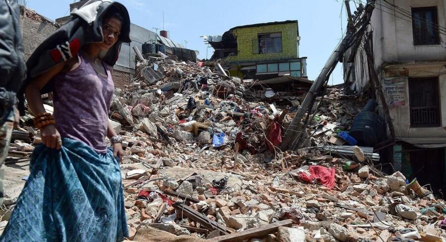 En kvinde går forbi smadrede huse i Kathmandu.