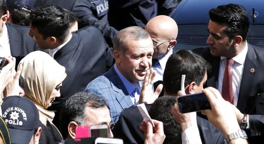 Tyrkiets premierminister Recep Tayyip Erdogan vinker til folkemængden (C) ved et valgsted i Istanbul.