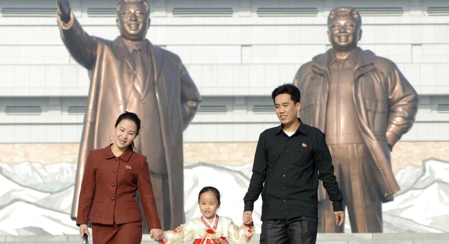 ARKIVFOTO. En nordkoreansk familie foran statuer af Kim Il-sung og Kim Jong-il. En ny bog giver et indblik i den mystiske og næsten hermetisk lukkede diktaturstat.