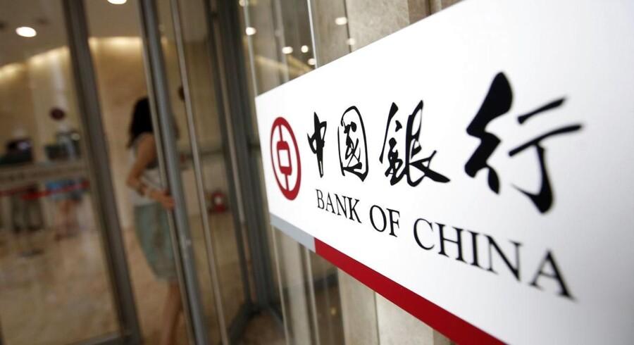 En kvinde på vej ind en kontorbygning tilhørende Bank of China. Bank of China udstedte d. 20 juni en pressemeddelelse, der afviste medierapporter om bl.a. insolvens og misligholdte lån.