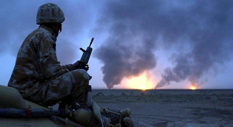 En britisk soldat skuer ud over en ukendt fremtid og en række brændende oliefelter i det sydlige Irak på invasionens første dag i 2003. Foto: Bruce Adams/AFP