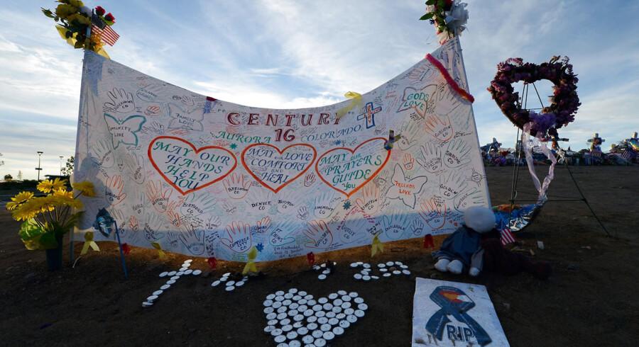 Folk mindes ofrene med bannere, blomster og lys i Aurora.
