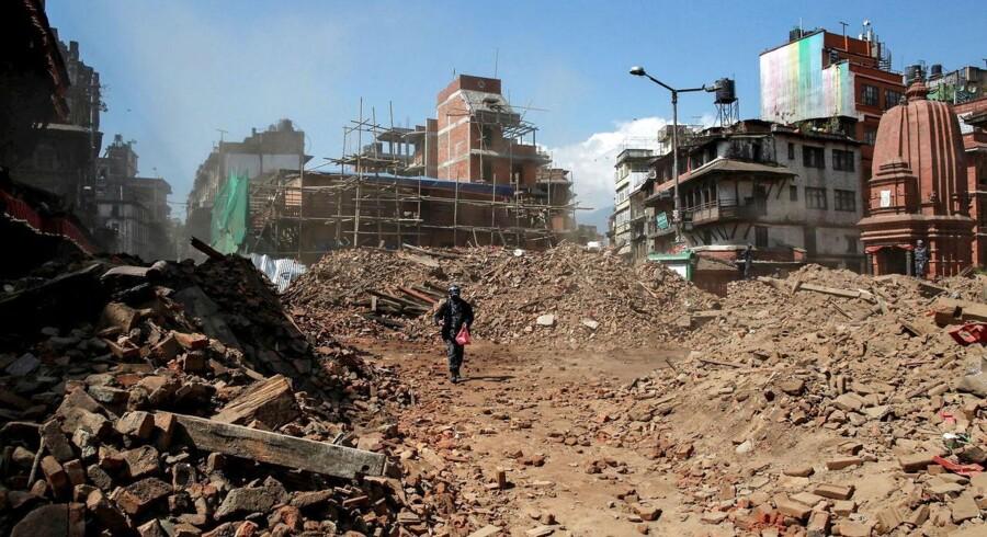 Kathmandu. En nepalesisk politibetjent går mellem murbrokkerne mandag efter lørdagens jordskælv.