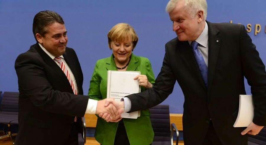 Formændene for henholdsvis SPD og CSU, Sigmar Gabriel (t.v.) og Horst Seehofer (t.h.), giver hinanden hånden på regeringsaftalen, som de har brugt de seneste fem uger på at forhandle med Angela Merkel (CDU) (i midten).