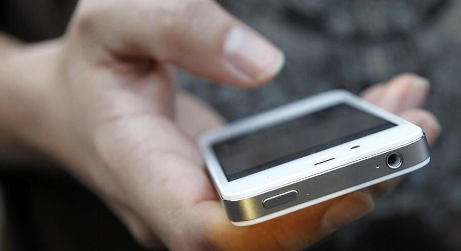 En kunde bruger sin nye Iphone 4S telefon efter at have hentet den i Appleforretningen i San Francisco.foto: REUTERS/Robert Galbraith