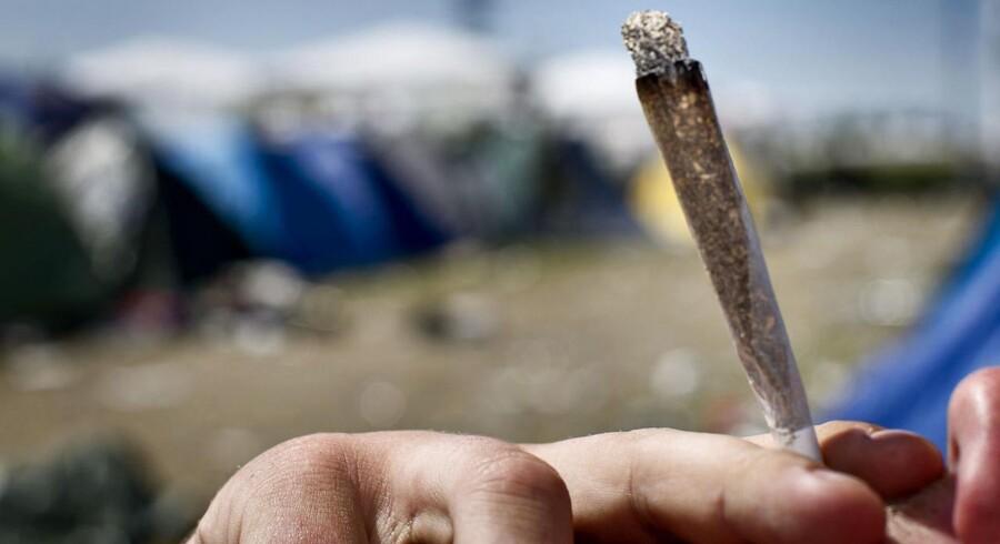 En festivalgænger ryger en joint på årets Roskilde Festival.